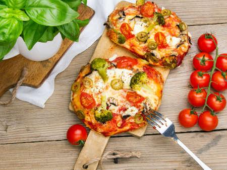 Lekkere Italiaanse zelfgemaakte mini-pizza's met broccoli, feta en olijven geserveerd op houten snijplank. Stockfoto
