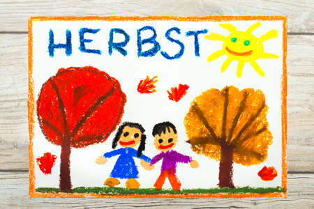 Photo of colorful drawing: German word Autumn, trees with red and orange leaves and smiling people,  Stock Photo