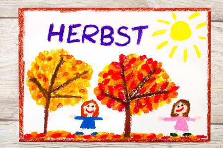 Photo of colorful drawing: German word Autumn, trees with red and orange leaves and smiling girls,
