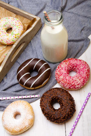 Bottle of milk and colorful donuts with chocolate and icing, selective focus Stock Photo