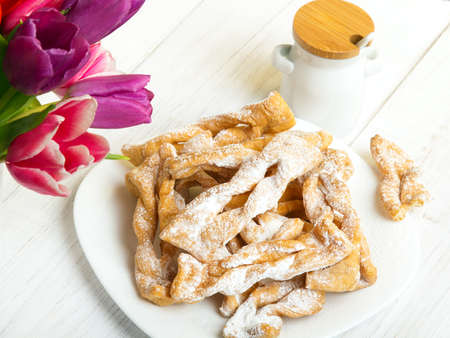 Faworki - Traditional Polish cookies served at Fat Thursday.  Cookies and tulip bouquet on white wooden background