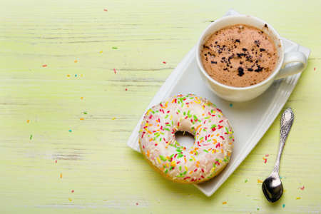Cup of coffee and tasty donuts with icing and chocolate on green wooden background, copy space
