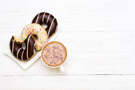 Cup of coffee and tasty donuts with icing and chocolate on white wooden background, copy space