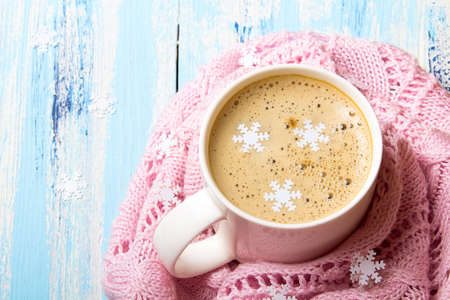 Tasty Christmas coffee or cocoa on blue wooden background and pink tablecloth. Copy space