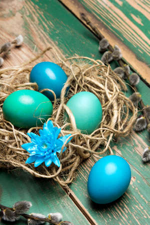 Easter background with eggs, nest and catkins on old wooden background, copy space