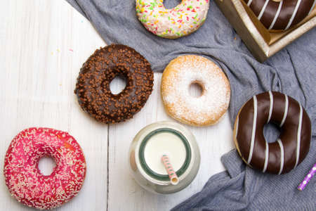 Bottle of milk and colorful donuts with chocolate and icing, selective focus Reklamní fotografie