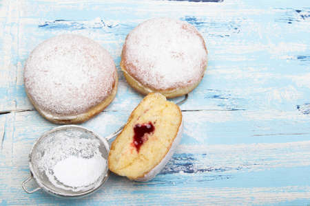 Traditional Polish donuts on wooden background. Tasty donuts with jam. Imagens