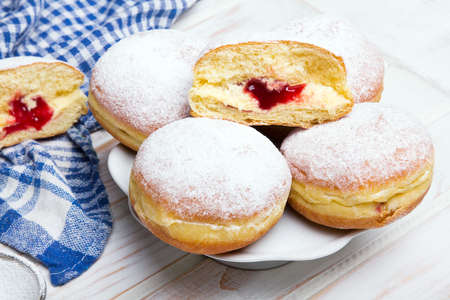 Traditional Polish donuts on wooden powder. Tasty doughnuts with jam.