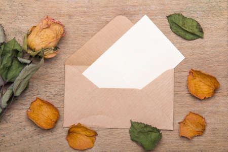 Dried orange roses and envelope on wooden background, copy space Banque d'images