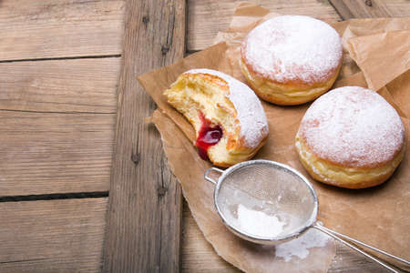Traditional Polish donuts on wooden background. Tasty doughnuts with jam. Reklamní fotografie