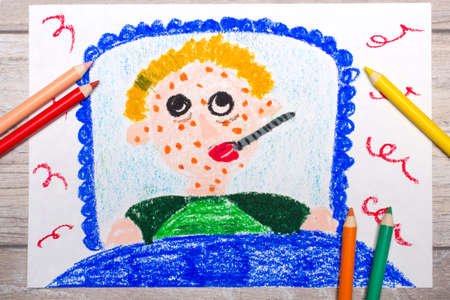 Photo of colorful drawing: sad sick boy lies in a bed. Boy with a rash on his face and a thermometer in his mouth