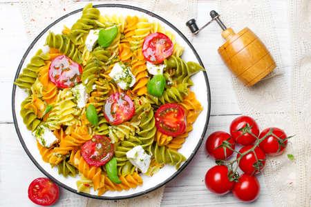 Italiaans eten - Salade met kleurrijke pasta, kerstomaatjes, fetakaas en verse basilicum op witte houten achtergrond