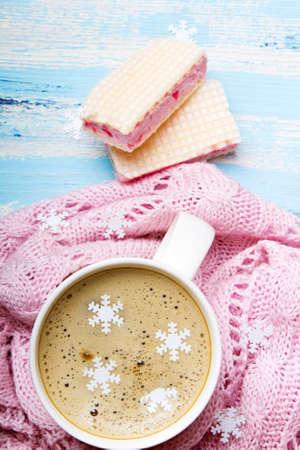 Tasty coffee or cocoa and sweet cookies on blue wooden background and pink tablecloth. Copy space