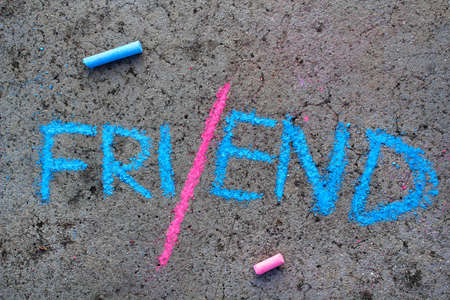 Colorful chalk drawing on asphalt:  end of friendship. Word FRIEND divided into half