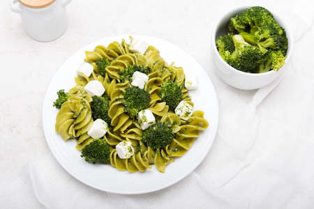 Tasty dinner. Green  pasta with broccoli, feta cheese and herb sauce on a white