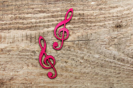 Red wooden treble clef on wooden background, copy space