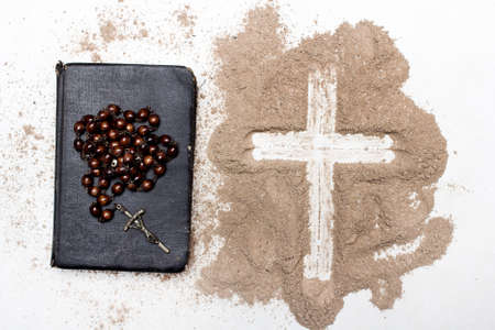 Old Bible, rosary and Cross of ash on white
