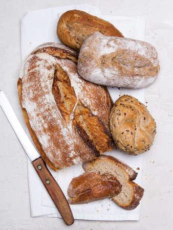 Savoureux pain noir et petits pains sur fond blanc, copiez l'espace. Produits de boulangerie, pain complet et petits pains bruns de blé entier