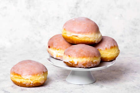 Traditional Polish donuts with frostng on light background. Tasty doughnuts with jam.