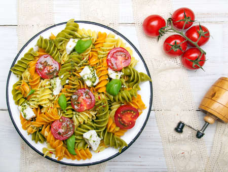 Italian food - Salad with colorful pasta, cherry tomatoes, feta cheese and fresh basil on white wooden background Stock fotó