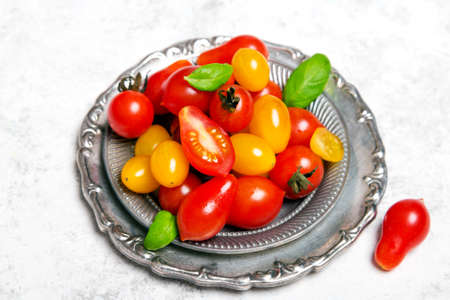 Colorful organic cherry tomatoes on silver plates, light