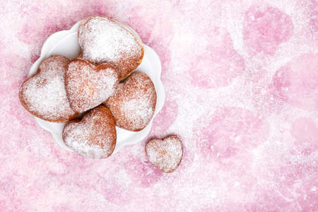 Homemade heart sheped donuts with powdered sugar on pnk background. Tasty doughnuts on cute pink pastel background