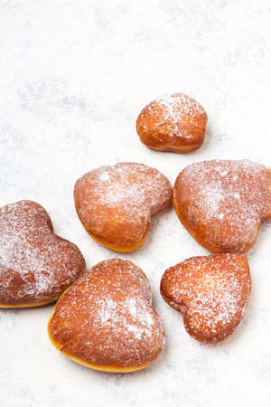 Homemade heart sheped donuts with powdered sugar on white background. Tasty doughnuts, copy space
