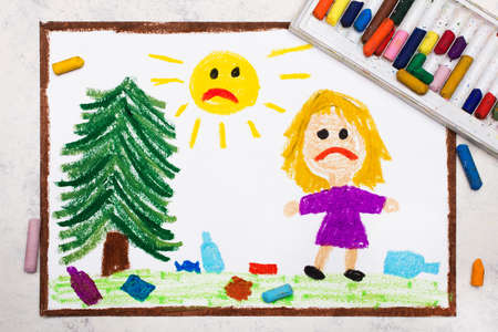 Sad girl is looking at trash in the meadow. Ecological problem of littering the planet . Photo of colorful drawing.