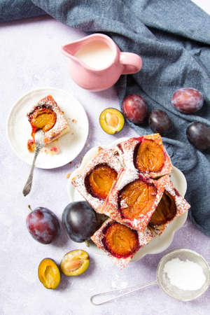 Tasty plum cake with pieces of fruit and powdered sugar on a light background Stock Photo