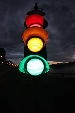traffic light: Fisheye photo from a traffic light. Photo was taken  at night. All lamps (red, yellow, green) are lighting. Stock Photo