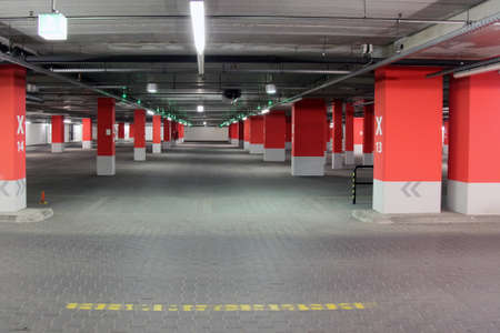 public space: Empty parking garage  Neon lighting, white and red reinforced concrete pillars, grey stone floor