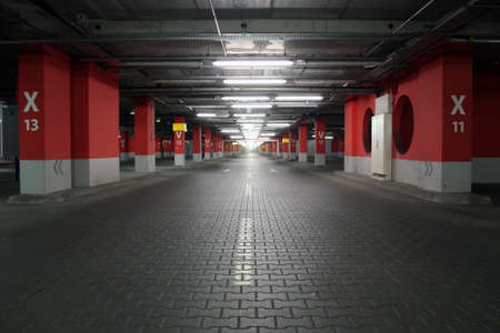 basement: Empty parking garage  Neon lighting, white and red reinforced concrete pillars, grey stone floor