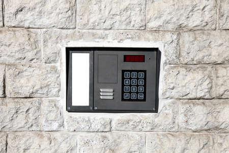 interphone: An intercom doorbell and access code panel on the wall.