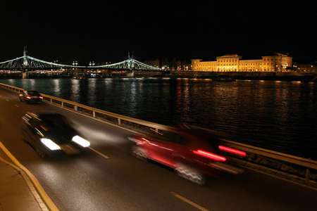 lighted: Cars are in motion on the quay in Budapest. The shore of the beautiful city is lighted on the background.
