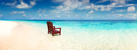 lear: Wooden chair standing in the sea on the beach invitation to rest on a deserted island alone, a wide panoramic view of the ocean