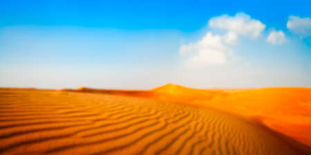 Blurred Wide panorama of sand and white clouds on a blue sky
