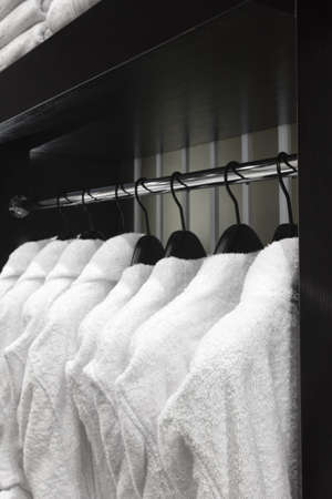 white bathrobes, pillows, towels, hanging in wooden closet of service room in hotel Stok Fotoğraf