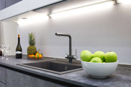 The interior of the modern kitchen is illuminated with a gray stone countertop with a luxury washbasin and mixer, fruit pineapple and tangerines, a bottle with red wine and two glasses. Banque d'images
