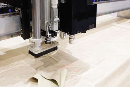 CNC machine for cutting fabrics textile materials and leather, laser marking and measurement. Modern footwear production.  Stock Photo