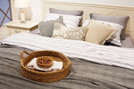 Nuts in a wicker basket on the bed, a gift for guests. luxury modern style bedroom in gray and blue tones