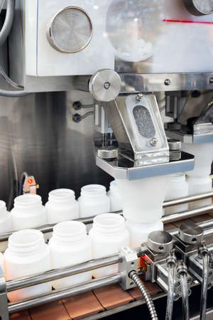 pharmaceutical industry, medicine pills are filling in the plastic bottle on production line machine conveyor at the medical factory. selective focus. 스톡 콘텐츠