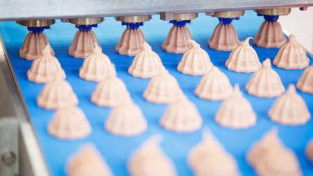 Cooking many sweet meringue on blue production line. sweet food concept. Reklamní fotografie