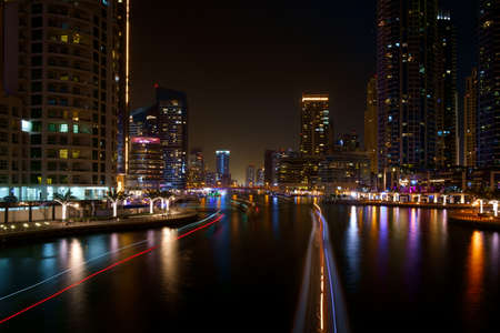 Night river traffic long tracers in Dubai UAE center along a city river with colorful reflections and blurred smok