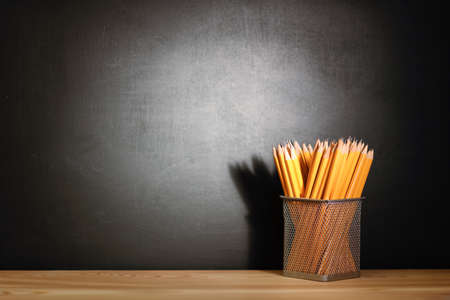 Pencils on a wooden school desk in front of a black chalkboard school. Education concept - the desk in the auditorium Stock Photo