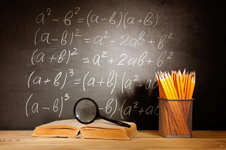 Old schoolbooks magnifier and pencils lying on a wooden school desk in front of a black chalkboard with Mathematical formulas school. Education concept - the desk in the auditorium Banque d'images
