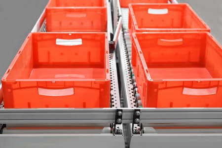 Red plastic containers on roller conveyors in an automated high bay warehouse. The boxes are used in the logistics chain transporting the produced goods. Selective focus. Stock Photo