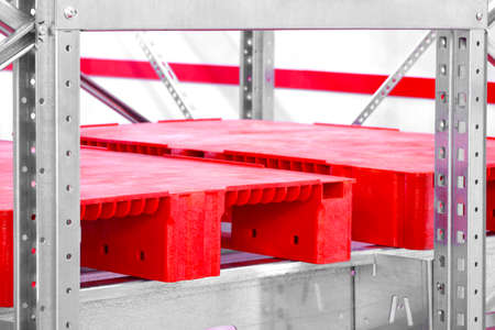 Empty red plastic pallets on racks in an automated warehouse complex