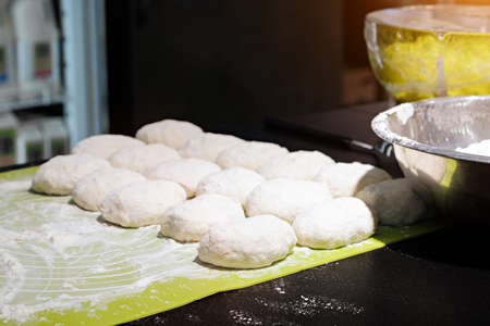Cooks roll the dough for baking, pieces of raw dough on the  Board Imagens