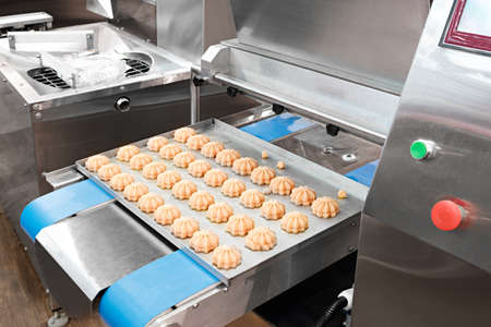 Cooking many sweet meringue on blue production line. sweet food concept. Stockfoto