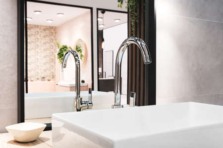 Luxury big faucet mixer on white rectangular sink in interior of beautiful beige gray bathroom and reflected in a large mirror